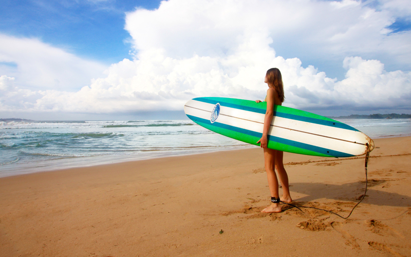 The i-escape blog / Discover Sri Lanka: the perfect island for a winter escape / Girl with surfboard on beach